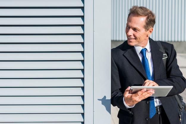 Uomo d'affari maturo felice che per mezzo della compressa digitale all'aperto