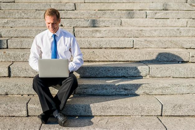 Uomo d'affari maturo felice che si siede sulla scala per mezzo del computer portatile all'esterno