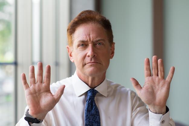 Uomo d'affari maturo imbarazzo che mostra gesto di arresto