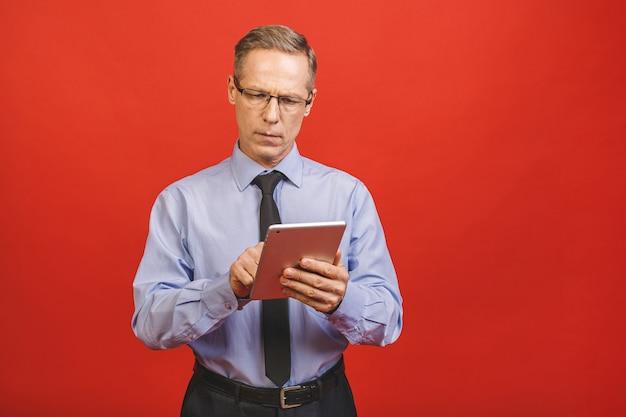 Uomo d'affari maturo invecchiato anziano moderno che guarda e che lavora alla compressa digitale isolata sulla parete rossa.
