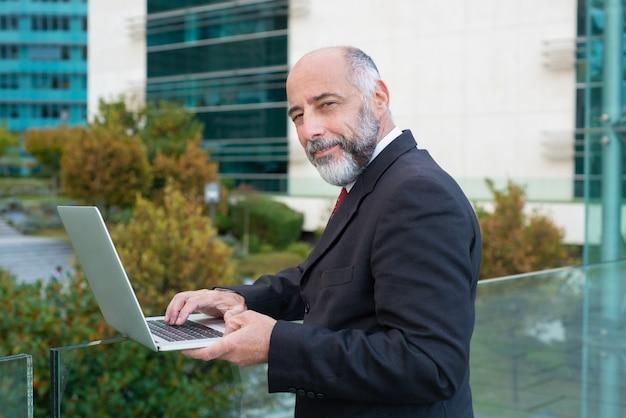 Uomo d'affari maturo positivo che per mezzo del computer portatile vicino all'edificio per uffici