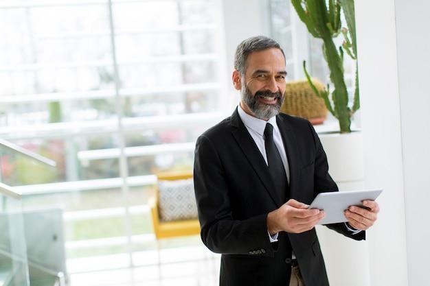 Uomo d'affari maturo sorridente bello con la compressa nel funzionamento dell'ufficio