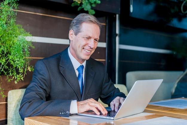 Uomo d'affari maturo sorridente che lavora al computer portatile sopra lo scrittorio in ristorante