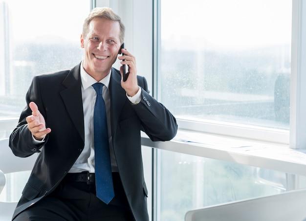 Uomo d'affari maturo sorridente che parla sul telefono cellulare