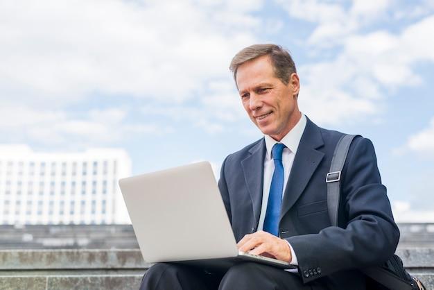 Uomo d'affari maturo sorridente che per mezzo del computer portatile all'esterno