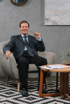 Uomo d'affari maturo sorridente che si siede sulla poltrona molle