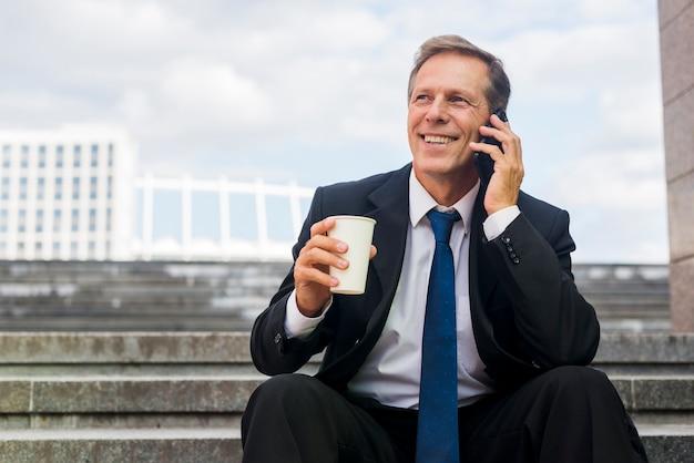 Uomo d'affari maturo sorridente con la tazza di caffè che parla sul telefono cellulare