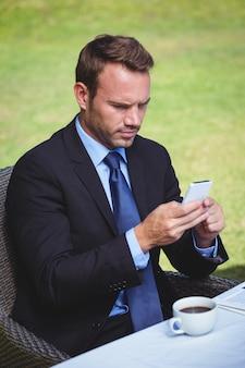 Uomo d'affari messo a fuoco che esamina il suo smartphone