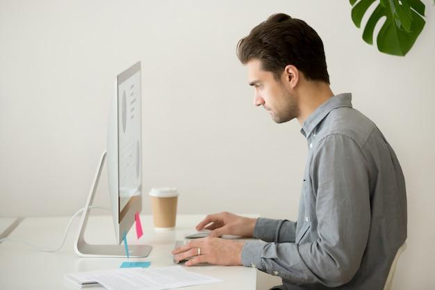 Uomo d'affari messo a fuoco che lavora al computer con le statistiche di progetto, vista laterale