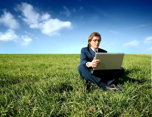 Uomo d'affari messo sul campo di erba che funziona con il computer portatile
