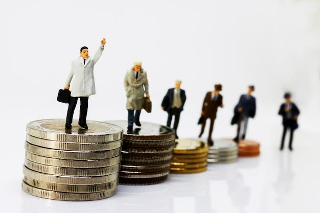 Uomo d'affari miniatura che cammina sul punto dei soldi delle monete