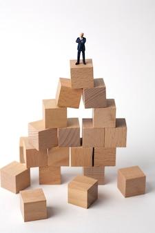 Uomo d'affari miniatura che sta sui blocchi di legno