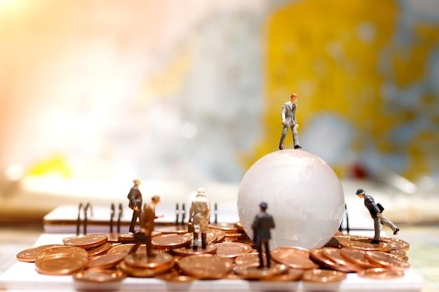 Uomo d'affari miniatura che sta sulla mappa di vetro del globo con la moneta.