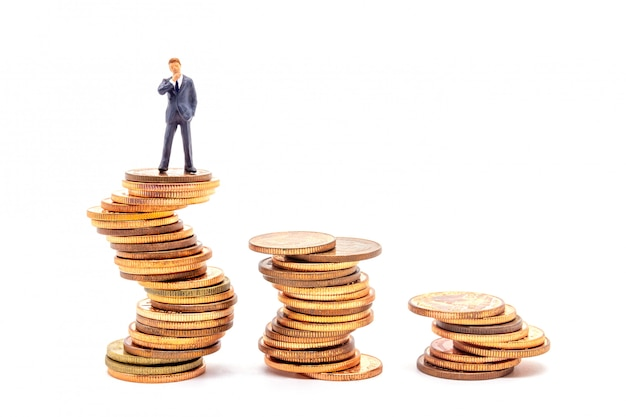 Uomo d'affari miniatura sulla pila sul mercato aziendale dell'incertezza bianca.