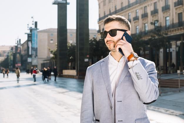 Uomo d'affari moderno che fa telefonata all'aperto