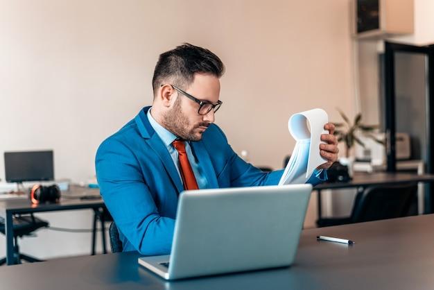 Uomo d'affari moderno che lavora ai documenti in ufficio.