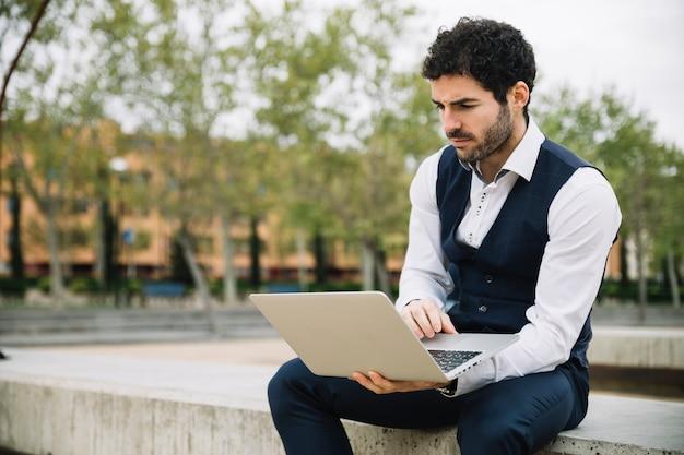 Uomo d'affari moderno che per mezzo del computer portatile all'aperto
