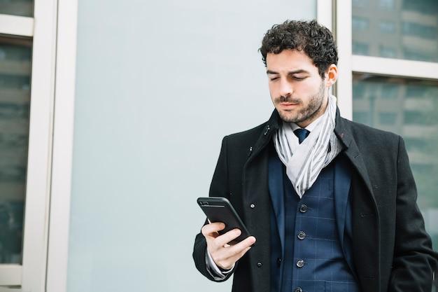 Uomo d'affari moderno che utilizza dispositivo all'aperto