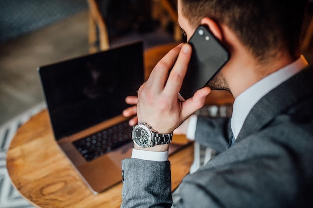 Uomo d'affari nel caffe che parla al suo telefono con il computer portatile