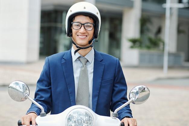 Uomo d'affari nel casco che si siede sullo scooter