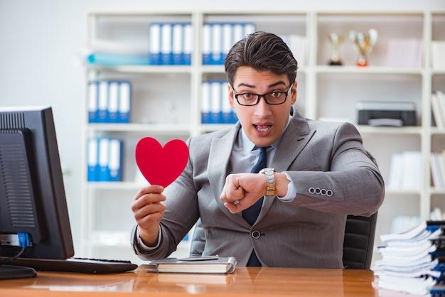 Uomo d'affari nel concetto del biglietto di s. valentino del san in ufficio