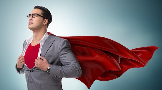 Uomo d'affari nel concetto di supereroe con copertina rossa