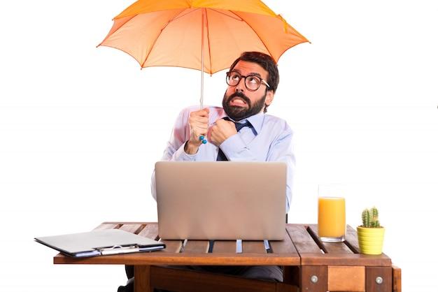 Uomo d'affari nel suo ufficio che detiene un ombrello
