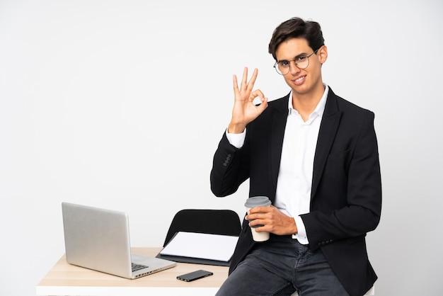 Uomo d'affari nel suo ufficio che mostra un segno giusto con le dita