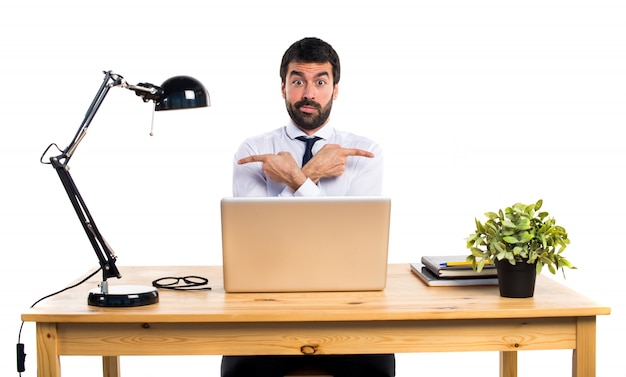 Uomo d'affari nel suo ufficio che punta ai laterali che hanno dubbi