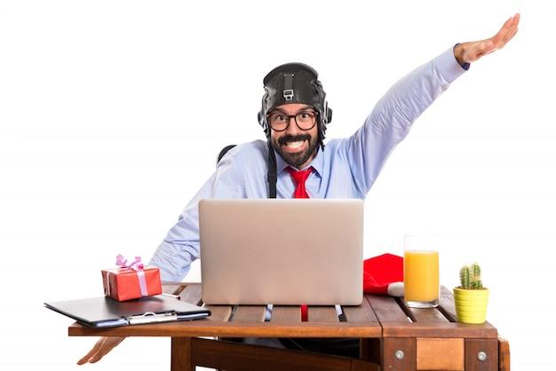 Uomo d'affari nel suo ufficio con cappello pilota