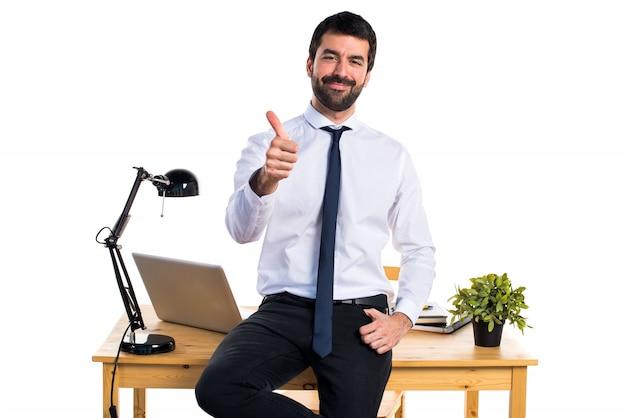 Uomo d'affari nel suo ufficio con il pollice in su