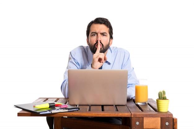 Uomo d'affari nel suo ufficio facendo gesto di silenzio