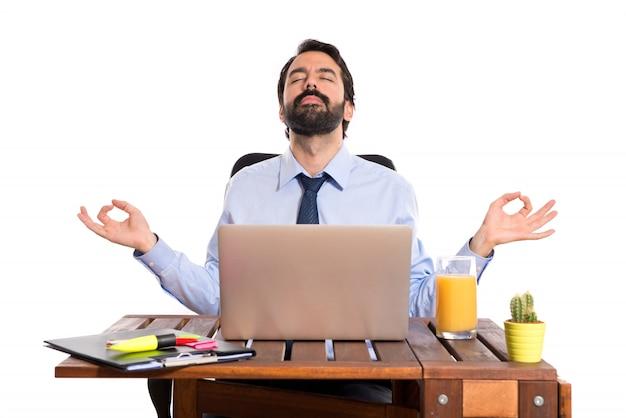 Uomo d'affari nel suo ufficio in posizione zen