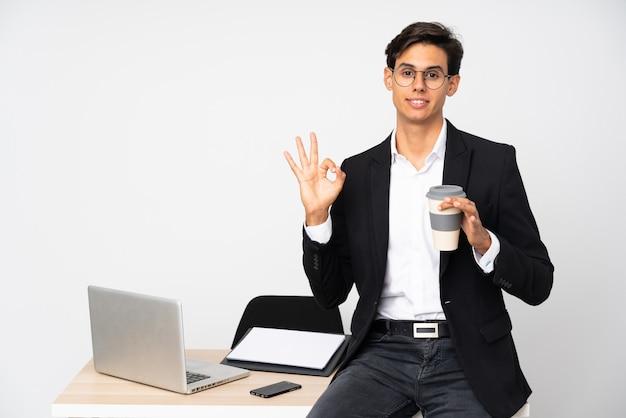 Uomo d'affari nel suo ufficio sopra la parete bianca isolata che mostra un segno giusto con le dita