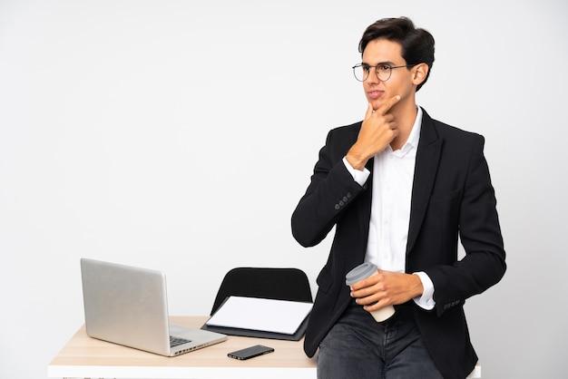 Uomo d'affari nel suo ufficio sopra la parete bianca isolata che pensa un'idea