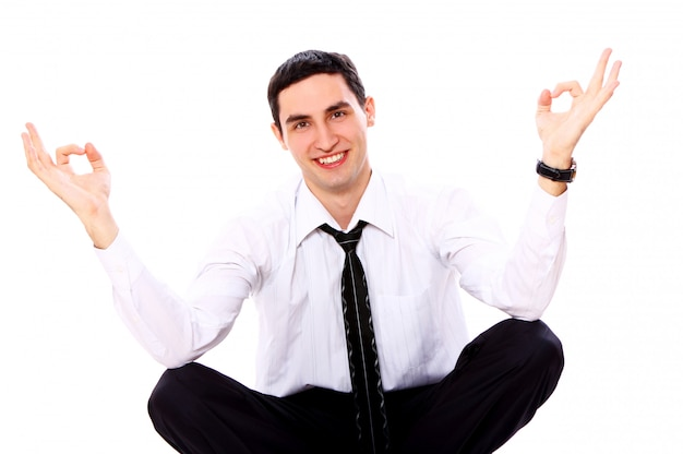 Uomo d'affari nella posa di yoga che mostra segno giusto