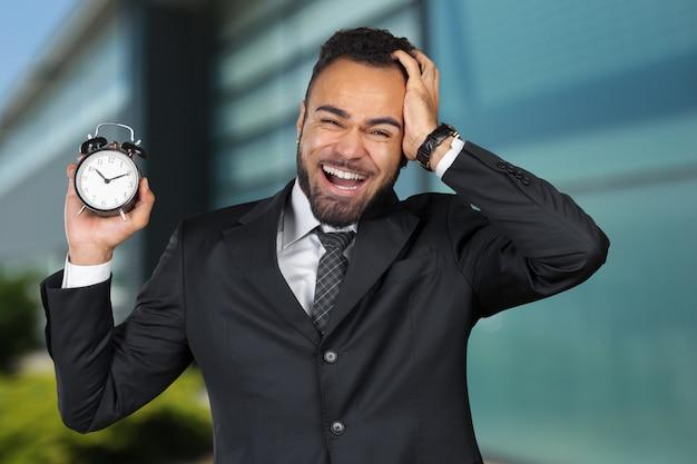 Uomo d'affari nero con sveglia. gestione del tempo
