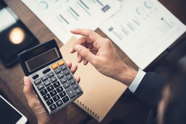 Uomo d'affari o consulente finanziario che utilizza il calcolatore che calcola e che analizza i dati
