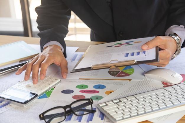 Uomo d'affari o ragioniere che lavora al calcolatore per calcolare il concetto di dati di affari.