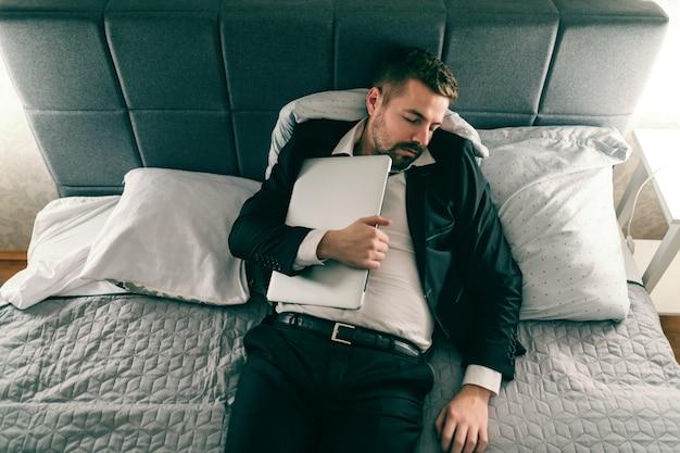 Uomo d'affari oberato di lavoro in vestito che dorme e sdraiato sul letto e che tiene il computer portatile sul petto.