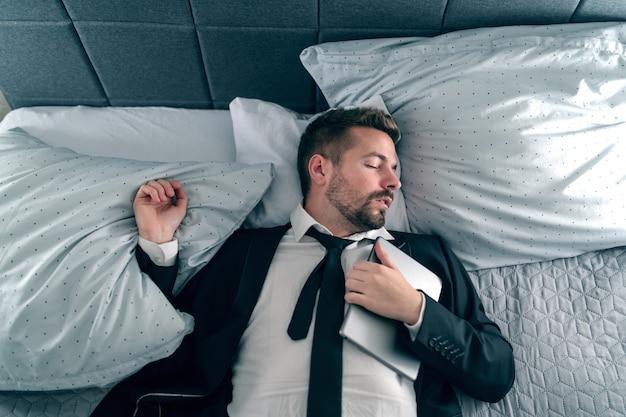Uomo d'affari oberato di lavoro in vestito che dorme e si trova sul letto e che tiene compressa sul petto.