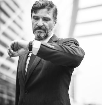 Uomo d'affari occupato che controlla il suo orologio