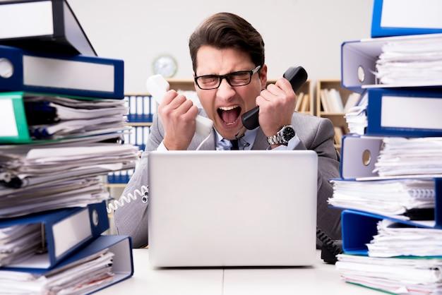 Uomo d'affari occupato sotto stress a causa di un lavoro eccessivo