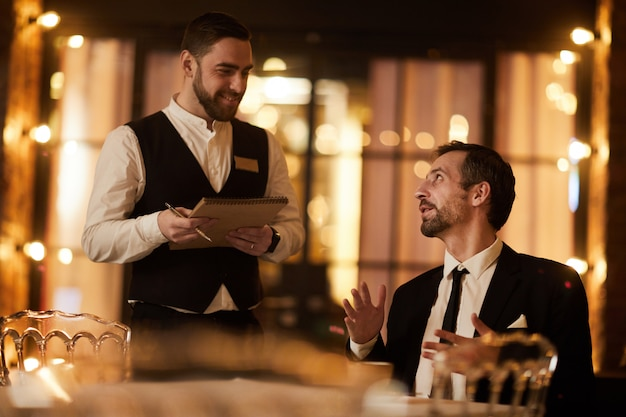 Uomo d'affari ordering food in ristorante