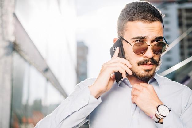 Uomo d'affari parlando al telefono e regolazione del colletto