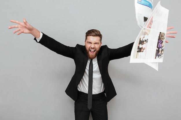 Uomo d'affari pazzo arrabbiato in vestito che grida e che getta giornale