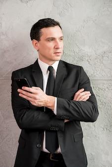 Uomo d'affari pensieroso con braccia incrociate guardando lontano