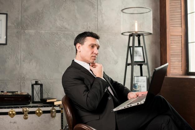 Uomo d'affari pensieroso con il computer portatile che lavora a casa
