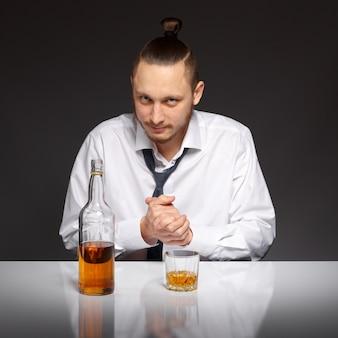 Uomo d'affari pensieroso con una bottiglia di alcol sul tavolo