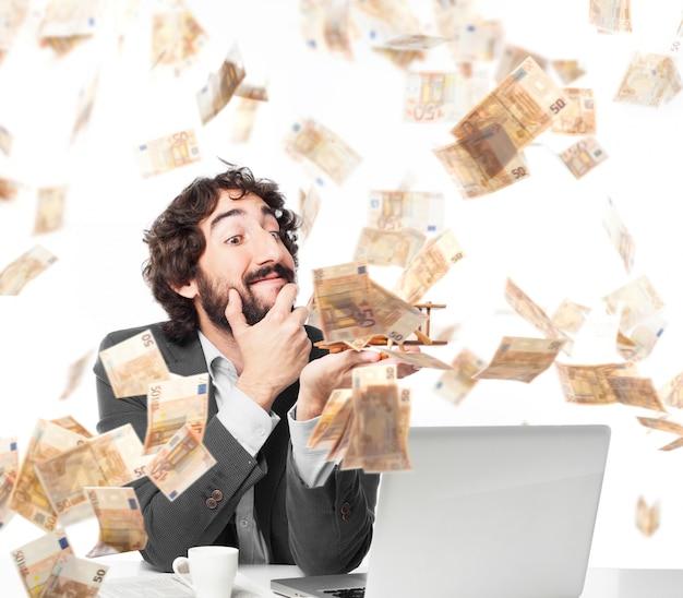 Uomo d'affari pensieroso sotto una pioggia di denaro